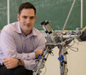 AMBER Lab Head Aaron Ames pictured with two-legged, humanlike robot