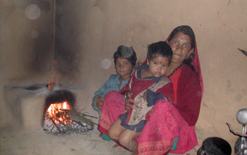 Image of a Indian woman and her two children with a dung or wood fuel cooking stove.