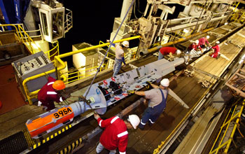Photo of several crew members prepping an instrument that will remain under the sea-floor.