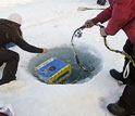 Photo of two people lowering a device into a hole in the ice.