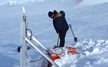researcher digging out a seismographic instrument in Antarctica