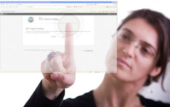 Photo of a woman touching her finger in the center of a circle on the NSF Digital Strategy web page.