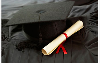Photo of a degree adjacent to a graduation cap on a black cloth.