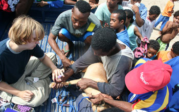 Photo of a dog's blood being take in the back of a pick-up truck mobbed by interested Papuans.