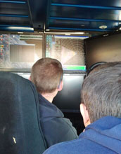 Image of scientists studying radar images of a blizzard inside the Doppler-on-Wheels.