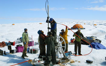 Team of scientists in Antaractica drilling a borehole