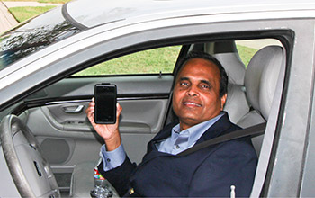 Photo of researcher Ram Dantu holding smart phone in his car.