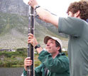 Photo of Curt Stager and Jay White retrieving a sediment core in a South African lake.