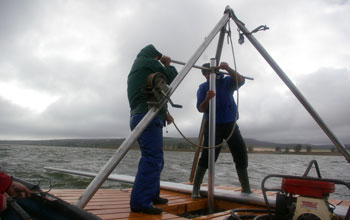 Photo of Curt Stager and Brian Chase collecting a sediment core with storm clouds overhead.