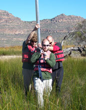 Photo of Christiaan King, Jay White and Brian Chase carrying a sediment core.