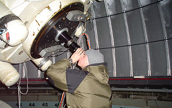 Student looking through large telescope