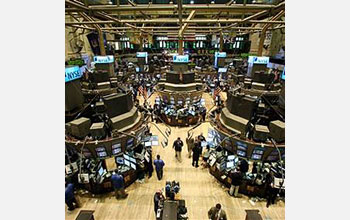 Photo of people walking and viewing computer monitors on the stock market floor.