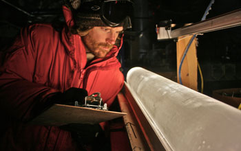 Scientist looking at an ice core from the West Antarctic Ice Sheet Divide coring site.