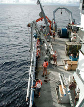 Team of men deploying a core barrel from a research vessel at sea.