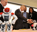Photo of Sen. Reid interacting with soccer robot dogs.