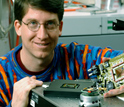 Photo of Steve Potter holding a device that creates a neural network - computer interface.