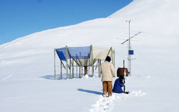 Photo of Alexander Kolodov and Mike LaDouceur examining an Arctic weathering station.