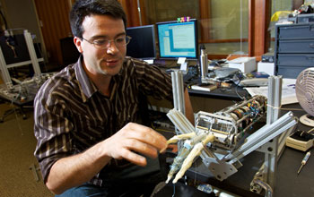 Image of a University of Washington doctoral student interacting with a lifelike robotic hand.