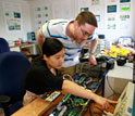 Image of two students with technology for improving the electricity transmission system.