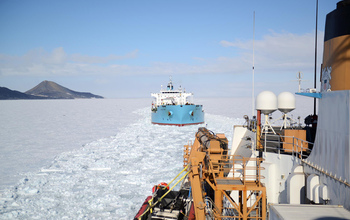 The USCGC Polar Star escorts a tanker through the sea ice of McMurdo Sound.
