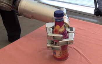 Image of Barrett Technology's advanced robotic Whole Arm Manipulator carefully grasping a bottle.