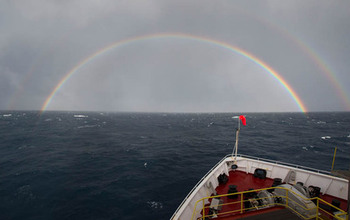 View of ocean horizon and rainbow from bow of research vessel.
