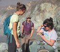 students in field analyzing rocks