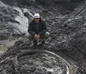 Image of scientist standing next to outcrop containing a mammoth tusk.