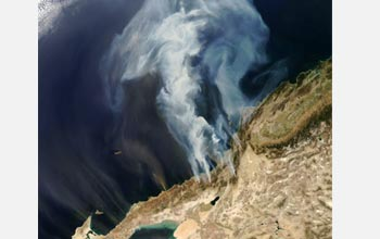 Satellite image of smoke from Southern California wildfires billowing over the Pacific Ocean.