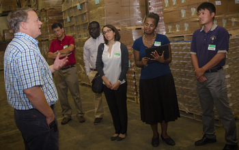 People stand in a food bank storage area.