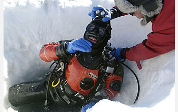 Photo shows a man helping another man prepare to leave the dive hole.