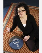 woman seated on rug next to blue, circular device labeled Roomba