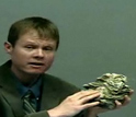 Shanan Peters holds a fossil coral and explains how sea level fluctuations cause mass extinctions.