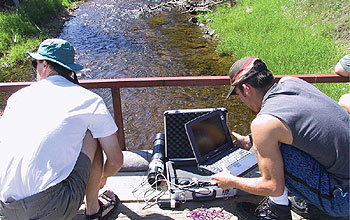 photo of two researchers near a stream