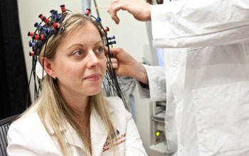 a young woman being prepared by a researcher for a brain imaging system.