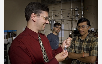 George Huber poses in the laboratory with Hakan Olcay and Tushar Vispute.