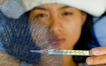 Photo of a young woman reading the temperature from a thermometer.