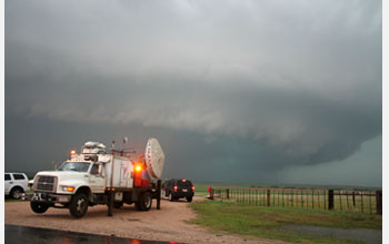 Photo of geoscientists using Doppler-on-Wheels to study tornado formation.