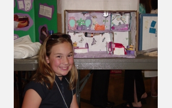 Young girl smiles at camera, science project in background.
