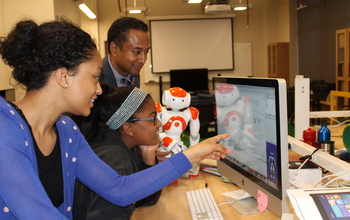 Photo of Andrew Williams instructing girls using the Choreographe visual programming environment