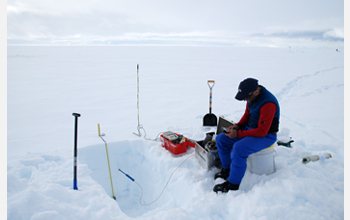 Photo of researcher Joel Harper making measurements on water flow through snow.