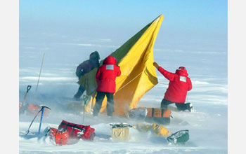 Photo of researchers setting up an Antarctic field camp.