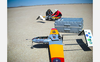 Research team members making adjustments to AUAVs, which carry miniature instruments.