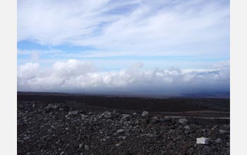 Photo of the twisting road, Mauna Loa's lava fields and clouds.