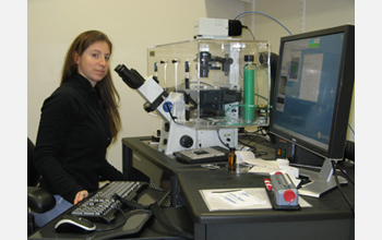 Photo of Susannah Gordon-Messer working on the fluorescence microscope used for her research.