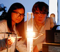 Photo of students observing a high-temperature furnace used to produce graphene on a silicon wafer.
