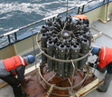 Overhead view of a water-sampling rosette on vessel and researchers