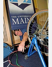 Photo of a man connecting a bicycle to a series of cables.