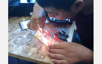 Photo of a student experimenting with using an Arduino microcontroller to power LEDs.
