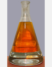 Photo of green gasoline siting above water in an Erlenmeyer flask.